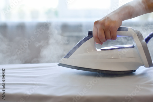 Fotografia Girl ironing shirt with steam station