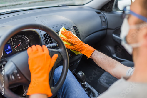 Fototapeta Man with face mask and rubber gloves cleaning car dashboard. Car detailing and valeting concept obraz