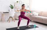At home sports. Sporty girl doing squats with dumbbells in living room