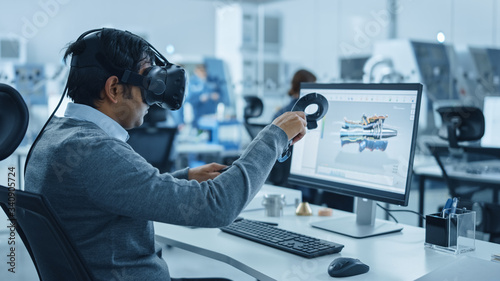 Fototapeta Modern Industrial Factory: Mechanical Engineer Wearing Virtual Reality Headset, Holding Controllers, Uses VR technology for Industrial Design, Development and Prototyping in CAD Software on Computer. obraz