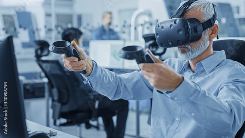 Vászonkép Industrial Design Engineer Wearing Virtual Reality Headset and Holding Controllers, Uses VR technology for Industrial Design, Development using Computer