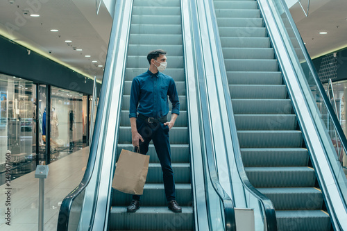 Fotomural lone man in a protective mask standing on the escalator steps