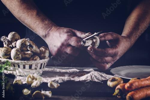 Obraz na plátně Cropped Image Of Chef Peeling Mushroom On Table