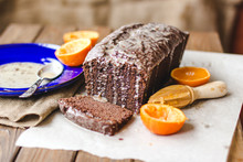 Chocolate Cupcake,white Icing, Orange Peel, Sauce On Light Paper, Wooden Background