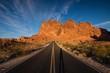 Road Leading Towards Rocky Mountain Against Blue Sky