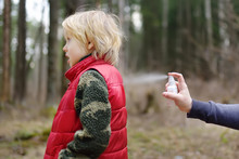 Woman Spraying Ticks Bite Repellents On Little Boy During A Walk In The Forest. Protect Children From Dangerous Insects While Hiking.