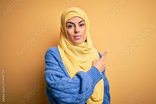 Young beautiful brunette muslim woman wearing arab hijab over isolated yellow ba Fototapete