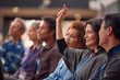 Businesswoman In Presentation At Conference Raising Hand To Ask Question
