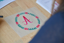From Above Of Drawn Beautiful Red Letter A In Colorful Circle Of Twigs On Wooden Table