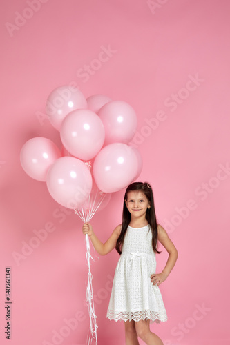 happy cute little child girl posing with pastel pink air balloons isolated over pink background. Beautiful happy kid on a birthday party.