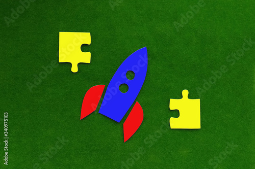 Rocket flying up, yellow puzzles on a green background Wallpaper Mural