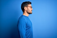 Young Handsome Man With Beard Wearing Casual Sweater And Glasses Over Blue Background Looking To Side, Relax Profile Pose With Natural Face And Confident Smile.