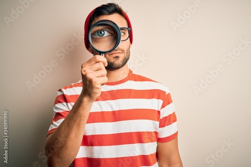 Obraz Young detective man looking through magnifying glass over isolated background with a confident expression on smart face thinking serious - fototapety do salonu