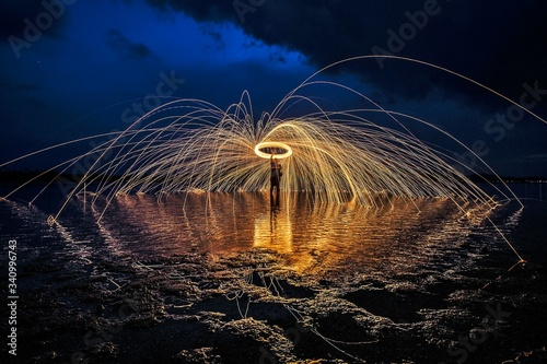 Fototapeta Man With Wire Wool On Shore Against Sky obraz