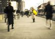 Motion blurred people walking on city street