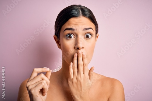 Young beautiful girl holding dental aligner over isolated pink background cover Canvas-taulu