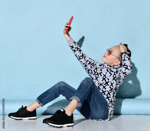 Photo Boy in sunglasses, jeans and hoodie, sneakers