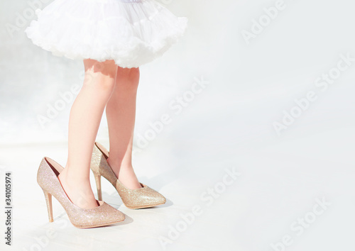 Fotografie, Obraz toddler baby girl is trying the shiny high heel shoes on