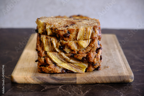 Fototapeta Homemade healthy banana bread served on a wooden board, black marble surface obraz