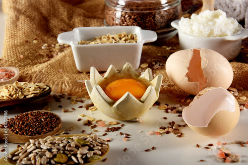 raw egg yolk accompanied by various seeds and egg shells Canvas Print