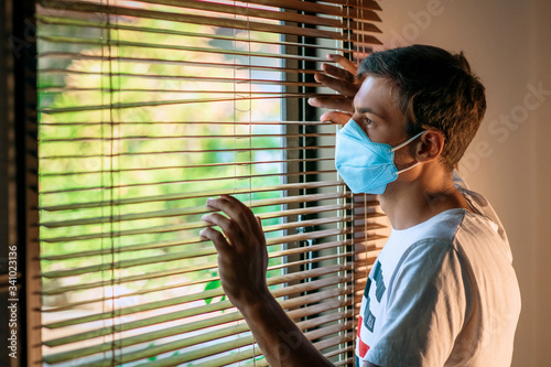 Sad man wearing face mask and looking out of window at home quarantine caused by coronavirus Canvas Print