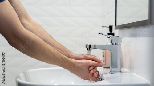 Mycie rąk w białej łazience.