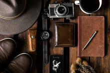 Vintage Photo Camera And Film. Wallet, Hat, Watch, Boots, Notebook, Coffee, Playing Cars And Plants On A Wooden Table.