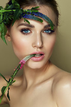 A Beautiful, Young, Romantic, Blue-eyed Girl Holds Blue Flowers Near Her Face, Biting A Bud Of A Pink Flower.