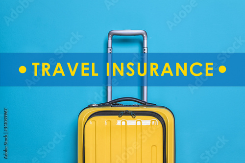 Photo Yellow suitcase and phrase TRAVEL INSURANCE on blue background