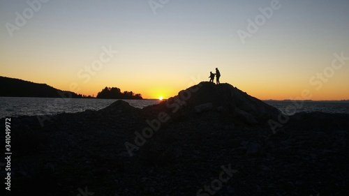 Fototapeta Silhouette People Overlooking Calm Sea At Sunset obraz na płótnie