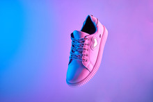 Trendy White Teenage Sneaker Flying In Trendy Neon Light. Levitation Shoe In Red, Blue Light. Creative Minimalism.