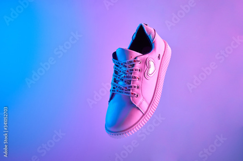 Obraz Trendy white teenage sneaker flying in trendy neon light. Levitation Shoe in red, blue light. Creative minimalism. - fototapety do salonu
