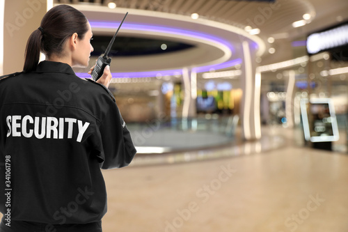 Carta da parati Security guard using portable radio transmitter in shopping mall, space for text