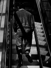 Low Angle View Of Man Walking On Escalator