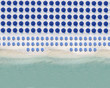 Aerial view of rows of blue beach umbrellas standing along sandy coastal beach