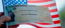COVID-19 Economic Stimulus Check On Blurred USA Flag Background. Relief Program Concept. Wide Photo.