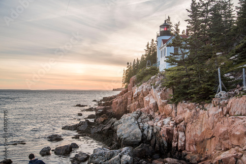 Photo view of light house on top of rock cliffs in acadia maine