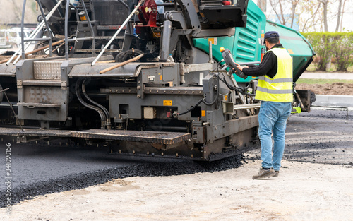 Photo The specialist adjusts the paver before laying the adjacent pavement
