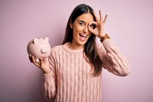 Young Beautiful Brunette Woman Holding Piggy Bank Saving Money For Retirement With Happy Face Smiling Doing Ok Sign With Hand On Eye Looking Through Fingers