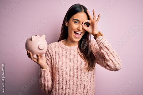 Fotografia Young beautiful brunette woman holding piggy bank saving money for retirement wi