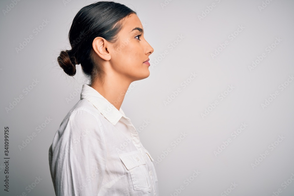Fototapeta Young beautiful brunette woman wearing casual shirt over isolated white background looking to side, relax profile pose with natural face with confident smile.