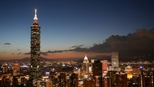Illuminated Taipei 101 In Cityscape Against Sky At Dusk
