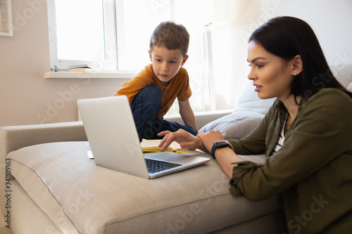 Obraz Cute little boy and his mother using laptop at home - fototapety do salonu