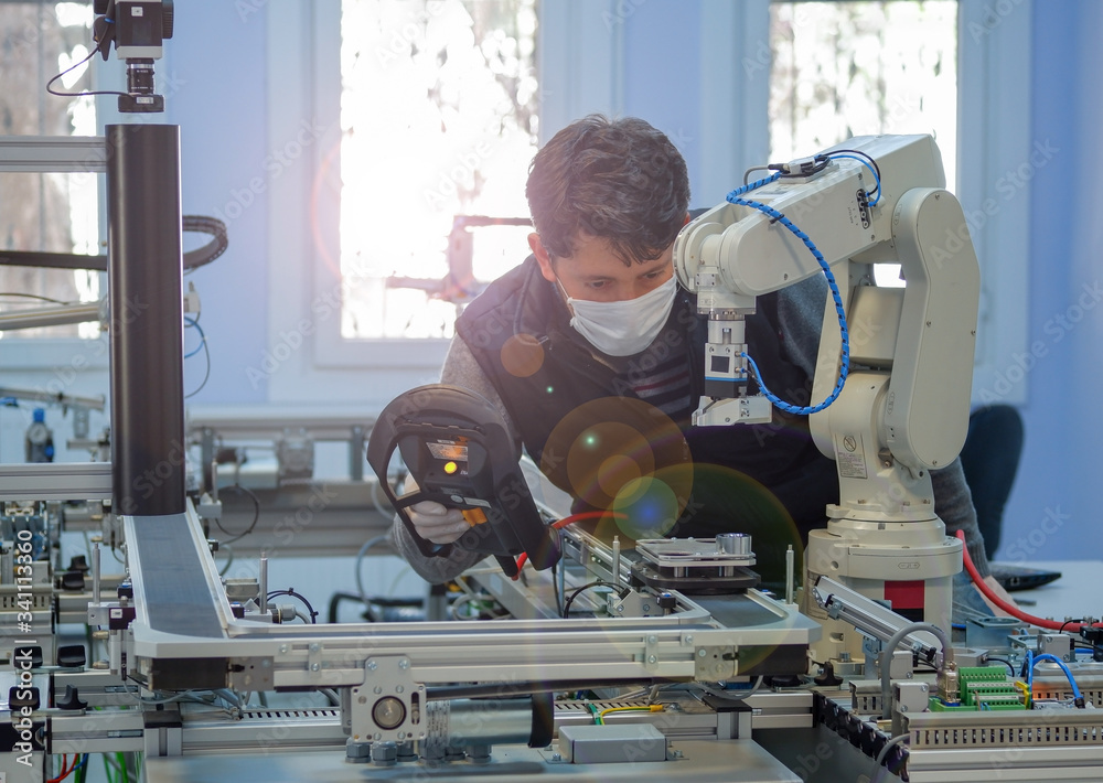 Fototapeta Man with surgical mask on face against COVID-19 ( Coronavirusis ) programming robot arm with control panel which is integrated on smart factory production line. industry 4.0 automation line.