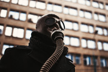 Low Angle View Of Person Wearing Gas Mask Against Building