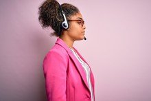 Young African American Call Center Agent Girl Wearing Glasses Working Using Headset Looking To Side, Relax Profile Pose With Natural Face With Confident Smile.