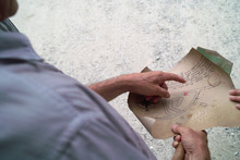 Close-up Of People Examining Map Outdoors