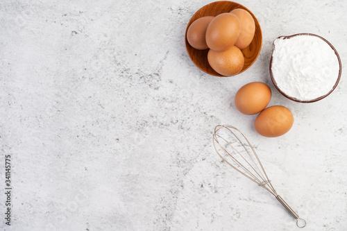 Eggs, tapioca flour in a cup and egg beater. Fototapeta