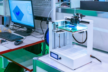 The 3d printer is next to the computer. 3d printer in the lab. Modern printing technologies. Creating three-dimensional images. Layer-by-layer printing of objects.