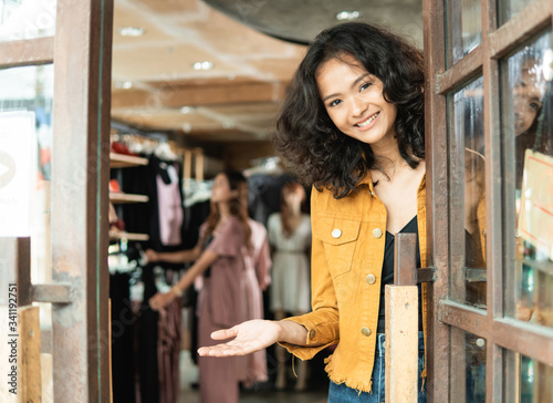 Foto beautiful young asian fashion shop owner at her boutique standing proudly welcom
